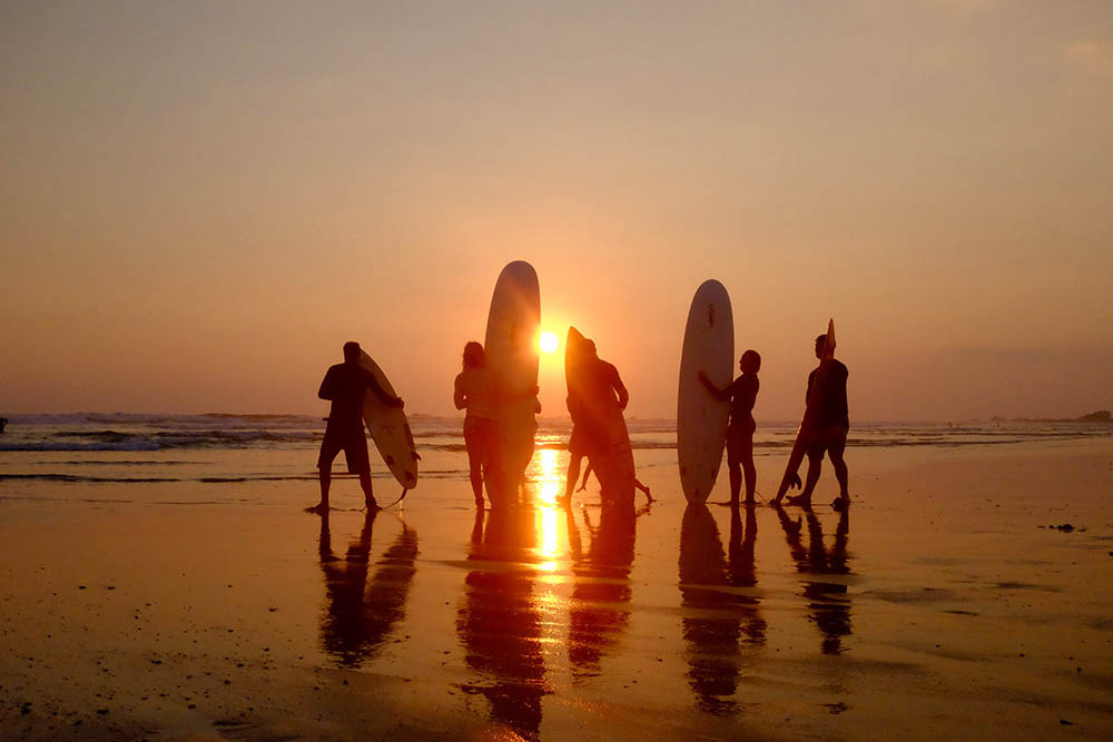 Surfers at Playa Guiones beach in Nosara, Costa Rica, by Andrew Day.