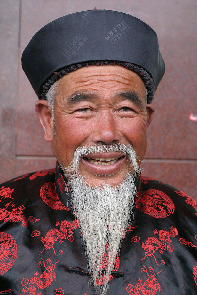 Man with a beard wearing a traditional costume in Shanghai, China, by Peter Ellegard.