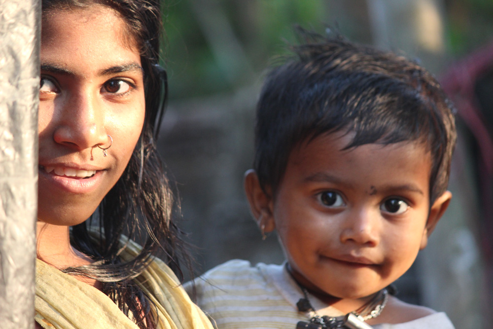 Girl with a toddler on her hip in Sreemangal, Bangladesh, by Tharik Hussain.