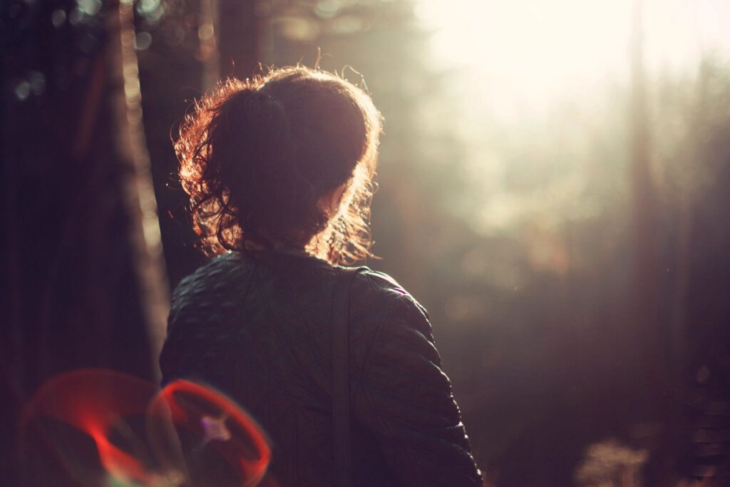 woman looking out at forest with bokeh